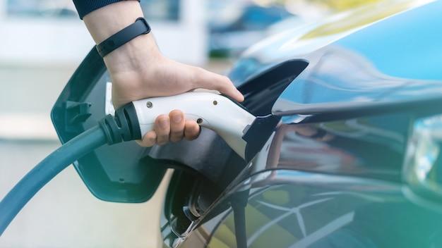 Мужчина подключает зарядное устройство к электромобилю на зарядной станции Бесплатные Фотографии