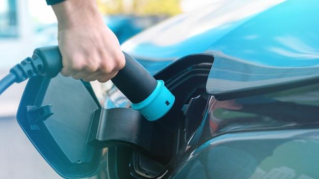 Мужчина подключает зарядное устройство к электромобилю на зарядной станции