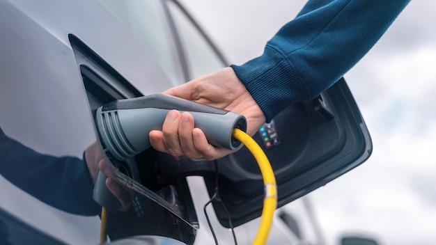 충전소에서 전기 자동차에 충전기를 연결하는 남자