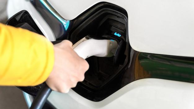 Человек подключает зарядное устройство к белому электромобилю