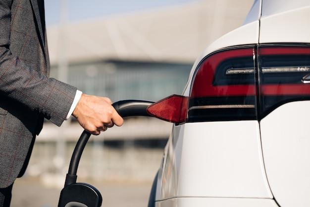 電子自動車充電ステーションで電気自動車を差し込む男