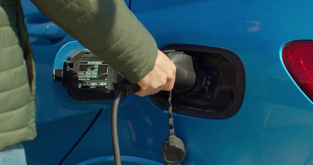 Мужчина подключает гибридный автомобиль у себя дома на зарядной станции. роскошный синий электромобиль подзарядки. экологически сознательный человек заряжает свой электромобиль.