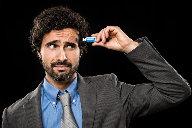 Man plugging a memory stick in his head