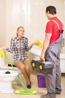 A man plumber speaks with a girl about repairing a sink.