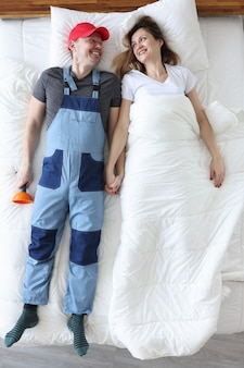 Man plumber and woman lying under blanket top view. husband for hour concept