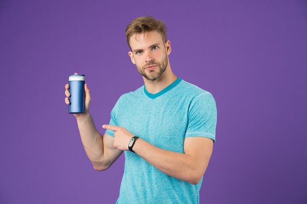 Man point finger at gel tube on violet background. bearded man hold shampoo bottle on purple background. skincare and hair care. health and healthcare. cosmetic for spa and bath or shower, copy space.