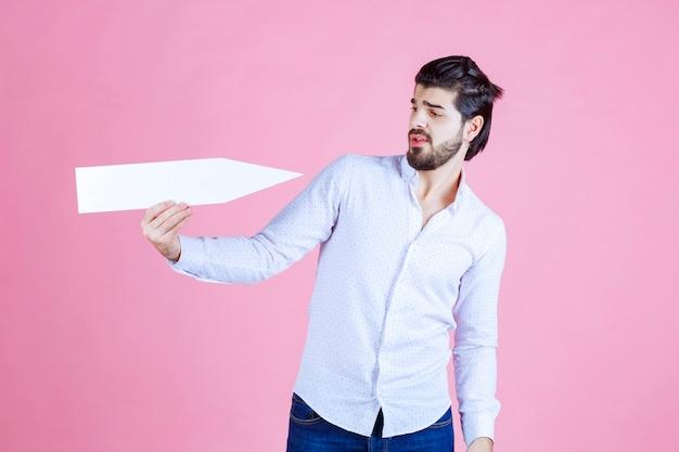 白い矢印を自分に向けている男。 無料写真