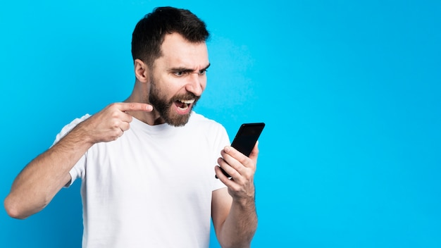 Man pointing angrily at smartphone