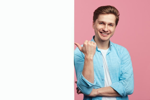 Человек, указывая на пустую белую стену рекламного щита, изолированную на розовом фоне
