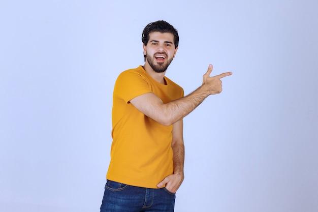 Человек, указывая на что-то или кого-то справа
