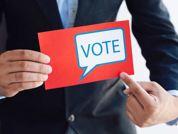 Man pointing to a ballot with a voting message