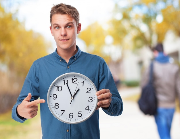 Man pointing to a big clock