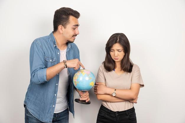Uomo che punta al globo terrestre accanto alla ragazza risentita.