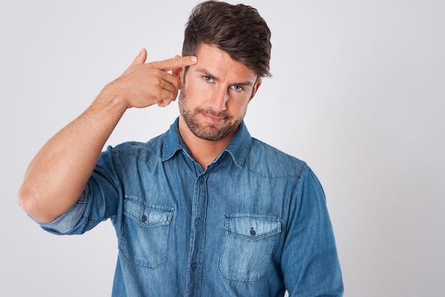 Man pointing finger gun gesture to head