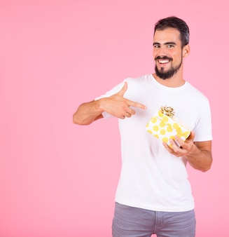 Man pointing finger on gift box with golden bow against pink backdrop