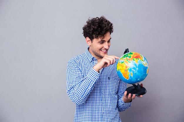 Человек указывая пальцем на глобус