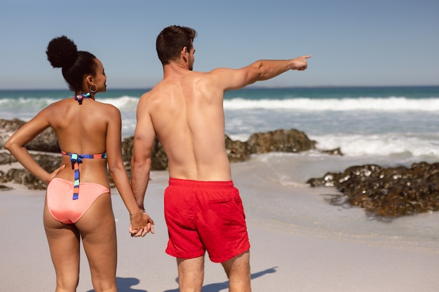 Man pointing finger and showing something to woman at beach in the sunshine