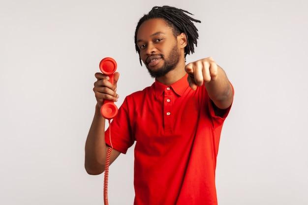 カメラに指を指して、赤いビンテージ固定電話の携帯電話を持って、電話に応答する男。