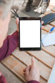 Man pointing finger toward digital tablet with blank white screen on wooden table