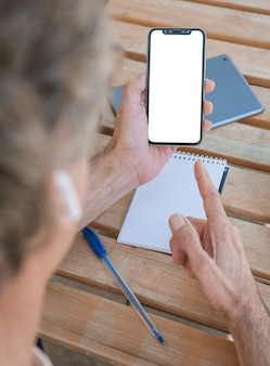 Man pointing finger toward mobile phone with blank white screen on wooden table