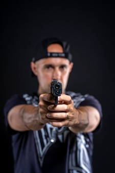 Man pointing gun at object, portrait on black background