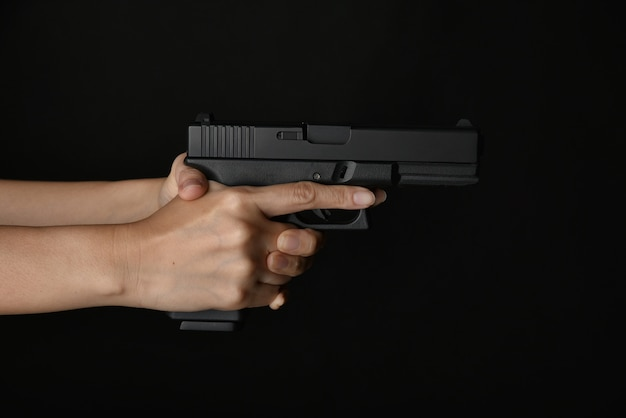Man pointing gun ready to shoot, killer with 9mm handgun pistol waiting for robbing the victim, weapon and violence crime concept.