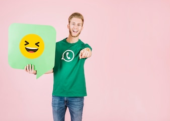 Man pointing his finger while holding speech bubble with smiling emoji