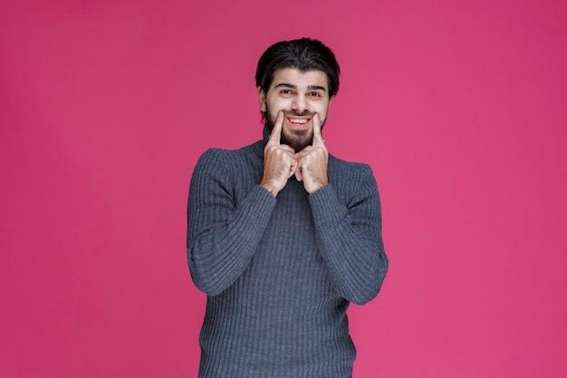 Мужчина указывает рот пальцами и спрашивает, улыбаясь.