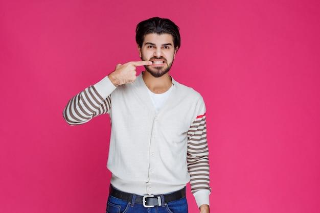 Man pointing his teeth or mouth with fingers meaning smiling or oral health.