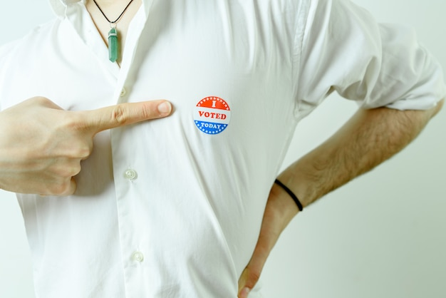 Man pointing to an i voted today sticker on his chest.
