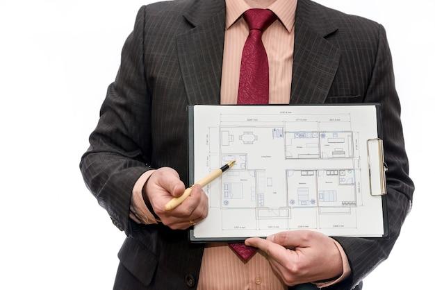 Человек, указывая на план дома, изолированные на белом фоне