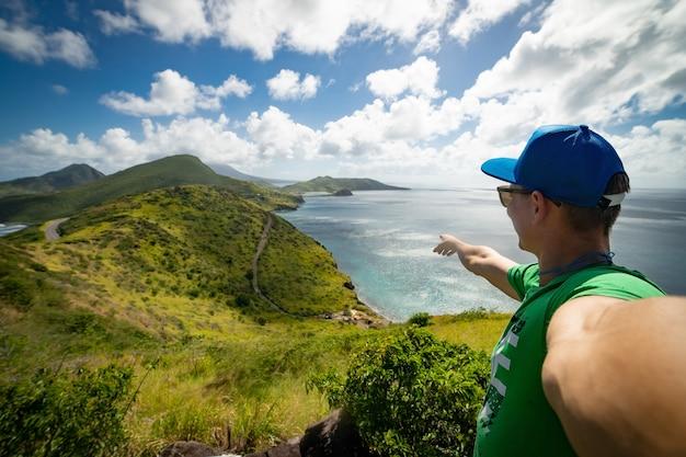 背景に雲と山と青い海の壮大な景色を指している男。休暇と旅行の概念。