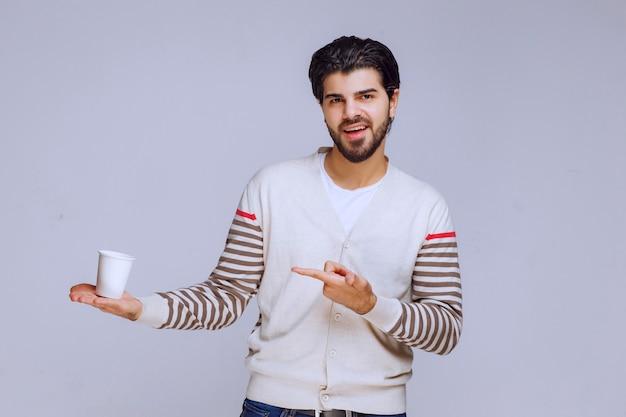 Uomo che indica la tazza di caffè in plastica in mano.