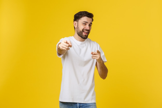 Man pointing showing copy space isolated on yellow wall. casual handsome caucasian young man.