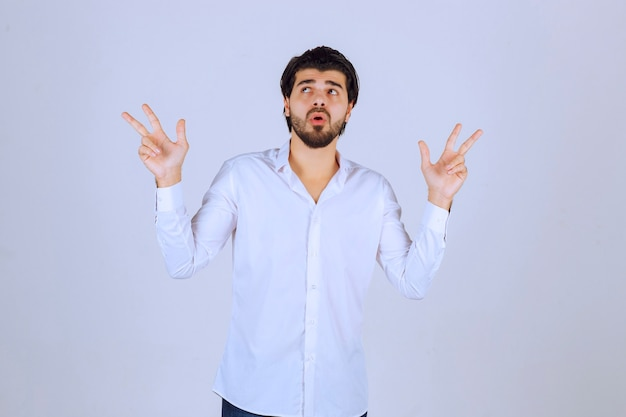 Man pointing upside or both sides in a confused way.