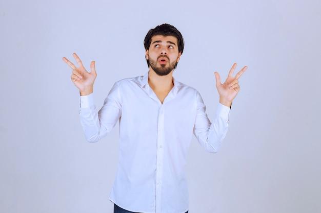 혼란스러운 방식으로 거꾸로 또는 양쪽을 가리키는 남자.