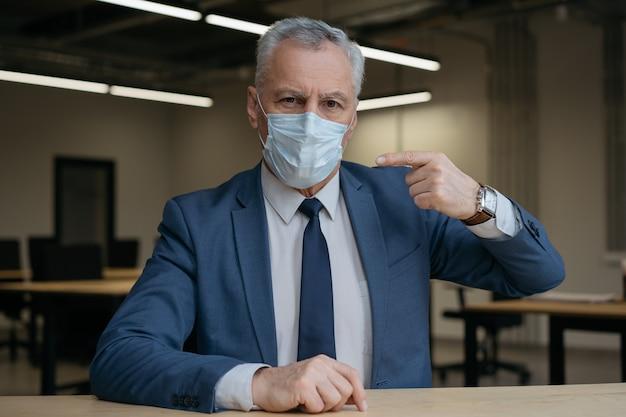 의료 얼굴 마스크에 손가락으로 가리키는 남자