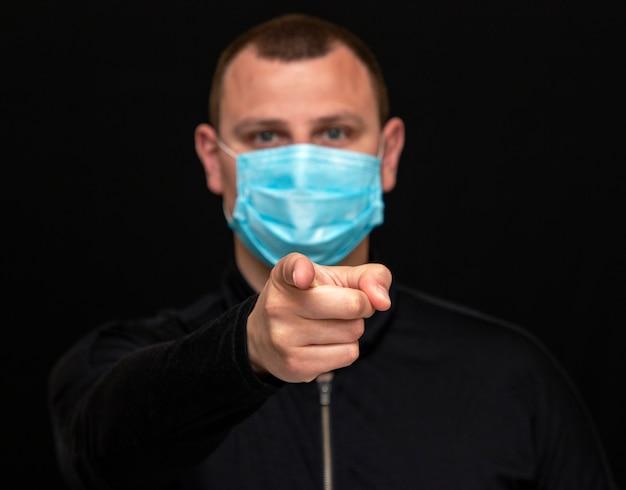Мужчина указывает пальцем на пациента в медицинской маске