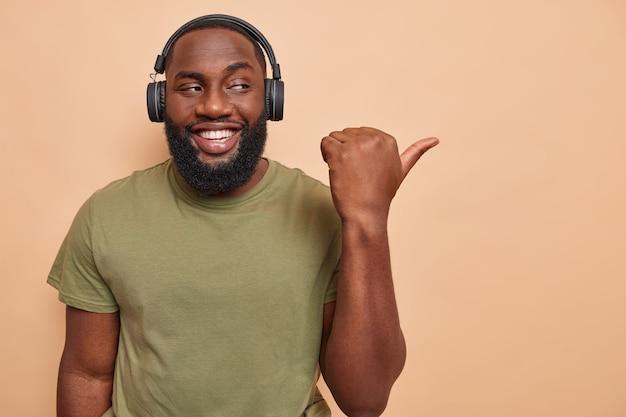 L'uomo indica lo spazio vuoto mostra il posto per la tua pubblicità ascolta la traccia audio nelle cuffie ha un umore felice sul beige