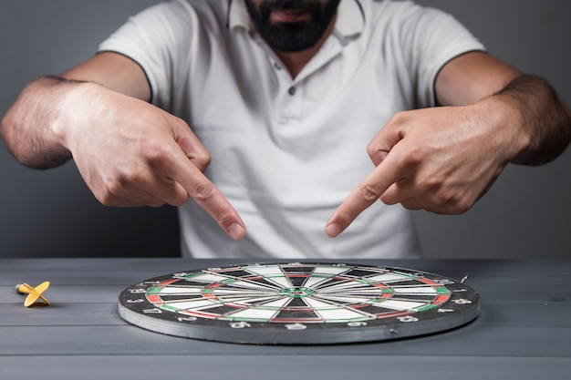 The man points to the center of the dart board. goal concept on gray wall Premium Photo