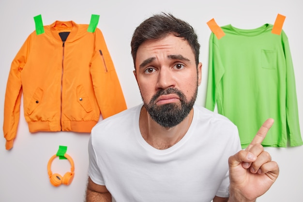 Man points at clothes plastered to wall feels sad poses around orange jacket green jumper and headphones makes choice promots something