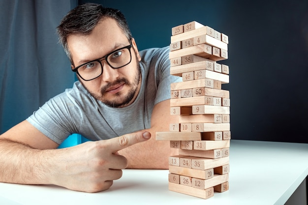 The man points to the column of the game of jenga. the concept of a mortgage, investment risks, economic crisis, economic instability.