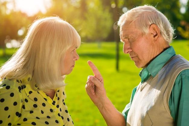남자는 여자에게 손가락을 가리킵니다.