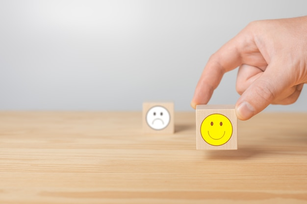 Man points his finger at wooden cube with positive face cube with sign negative face icon is blurred