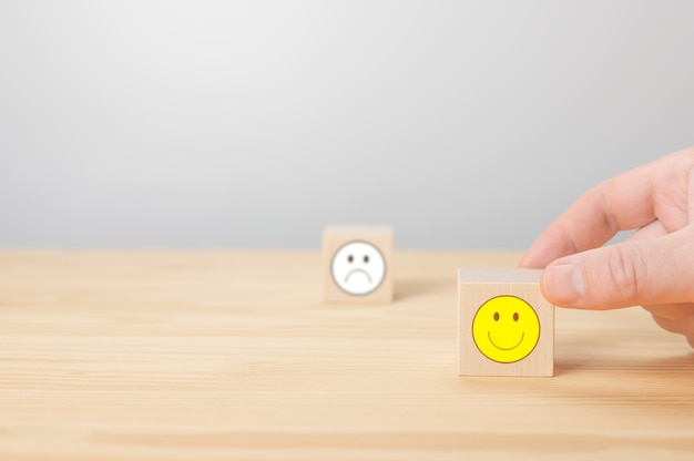 Man points his finger at a wooden cube with positive face cube with sign of negative face icon is