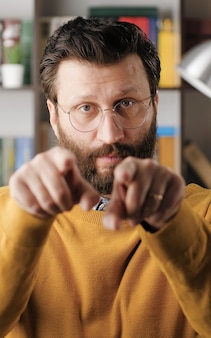 Man points his finger to you. serious frowning handsome bearded man with glasses looking at camera and points his finger in camera. close-up view