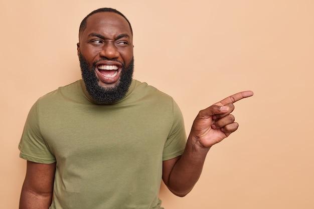 L'uomo punta il dito indice da parte indica via con espressione felice vestito casualmente sul beige