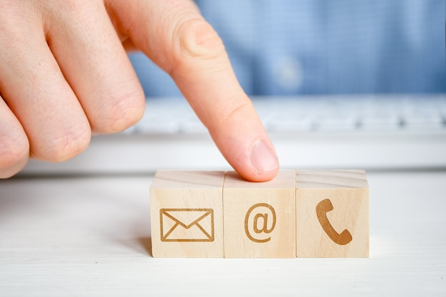 A man points to a wooden cube with the image of an email symbol next to a telephone and a letter with his hand. contact  for communication.