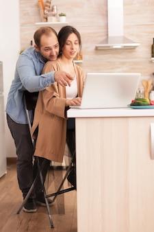 아내가 아침 식사를 위한 건강한 요리법을 찾고 있는 동안 남자는 부엌에서 노트북을 보고 있습니다. 현대적인 wi-fi 무선 인터넷 기술을 사용하여 집에서 사랑하는 부부의 행복한 사랑의 쾌활한 낭만적인