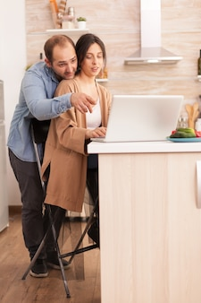 Man poiting at laptop in kitchen while wife is searching for healthy recipe for breakfast. happy loving cheerful romantic in love couple at home using modern wifi wireless internet technology